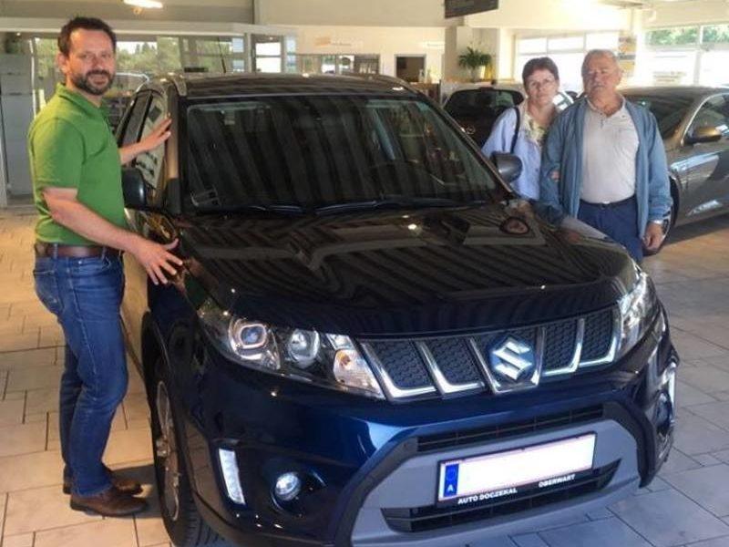 Verkaufsberater Herr Weinhofer gratuliert Familie Samer zum neuen Suzuki Vitara SE in sphere blue und wünscht eine gute und sichere Fahrt!